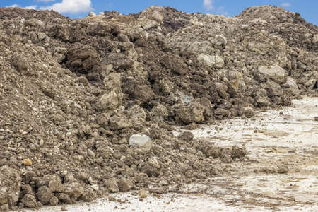 dirt ground: Construction dirt pile under blue sky and clouds Stock Photo