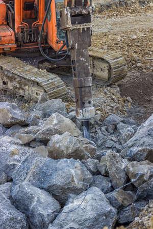 smashing: Excavator mounted hydraulic jackhammer used to break up concrete. Hydraulic breaker for smashing rocks. Selective focus.