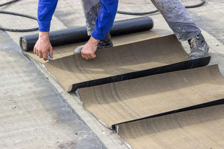 ruberoid: Insulation worker cutting insulation bitumen material rolls, insulation tar material over concrete slabs to keep water out.