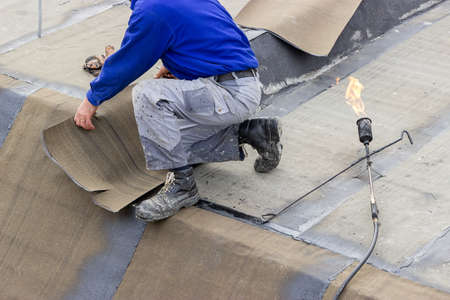 Insulation worker with propane blowtorch at floor slab insulation work. Worker heating and melting roll of bitumen roll. photo