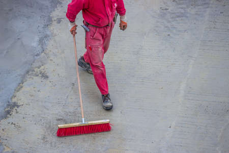 Worker cleaning concrete slab surface with a broomstick. Janitor with broom at construction site.