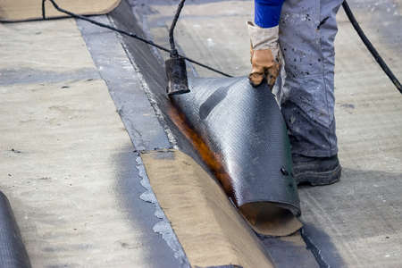 roofing membrane: Insulation worker with propane blowtorch at floor slab insulation work. Worker heating and melting bitumen felt. Stock Photo