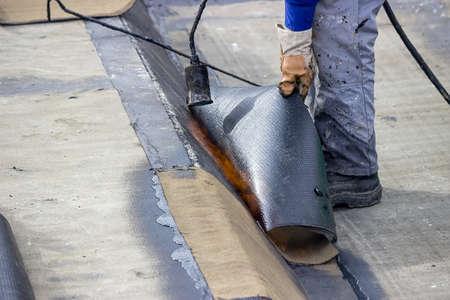 Isolierung Arbeiter mit Propan Lötlampe auf Bodenplatte Isolierarbeiten. Worker Erhitzen und Schmelzen Bitumen fühlte. Standard-Bild - 41489419