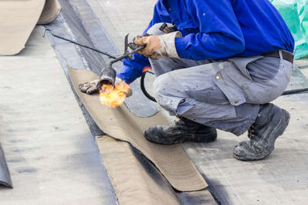 waterproofing: Insulation worker with propane blowtorch at floor slab waterproofing works. Worker heating and melting bitumen felt. Water proofing of concrete structure.