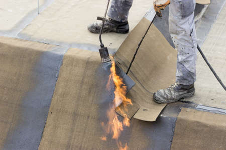 tar felt: Insulation worker with propane blowtorch at floor slab insulation work. Worker heating and melting roll of bitumen roll. Stock Photo