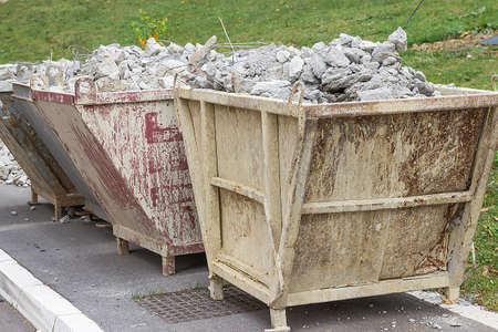 trash container: Full container of concrete debris. Trash container full of concrete debris.