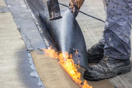 ruberoid: Insulation worker with propane blowtorch at floor slab insulation work. Worker heating and melting bitumen felt. Stock Photo