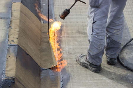 tar felt: Insulation worker with propane blowtorch at floor slab insulation work. Worker heating and melting bitumen felt. Stock Photo