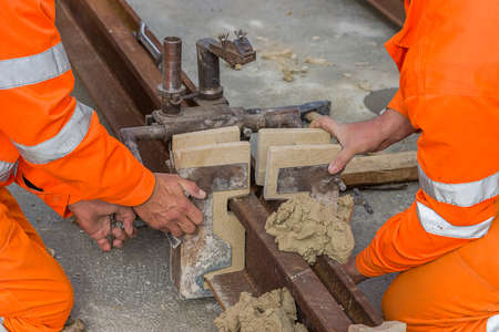 sand mold: Worker installing mould and using mould material on tram rail before thermit welding process.