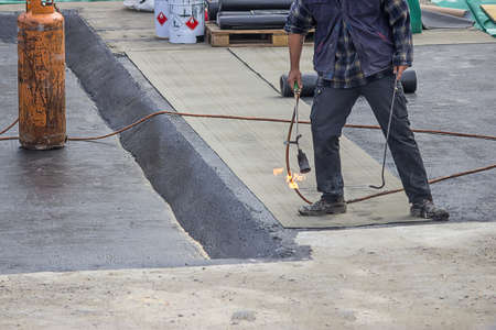 tar felt: Builder worker at floor slab insulation work with propane blowtorch, tar barrier over concrete slabs to keep water out.