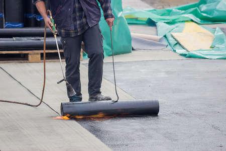 tar felt: Builder worker at floor slab insulation work, tar barrier over concrete slabs to keep water out