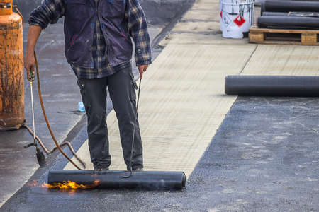 tar felt: Builder worker at floor slab insulation work, insulation tar material over concrete slabs to keep water out.