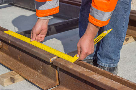 Preparation for rail welding process. Tramway track worker worker measures rail gap in the street.