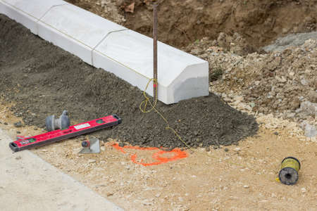 Tools for installing concrete curb stone and string with metal stakes to level at sidewalk construction site. Selective focus. photo