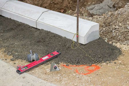 and the stakes: Tools for installing concrete curb stone and string with metal stakes to level at sidewalk construction site. Selective focus. Stock Photo