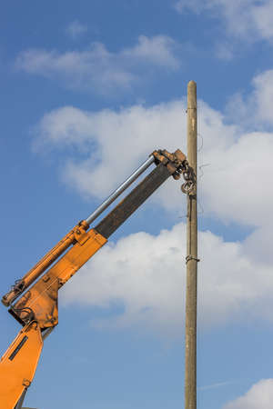 telephone pole: wooden telephone pole hangs vertically in the air from a yellow crane. Crane hook lifting the wooden telephone pole out.