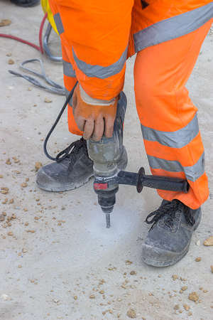 Worker drilling into concrete and wearing proper safety equipment