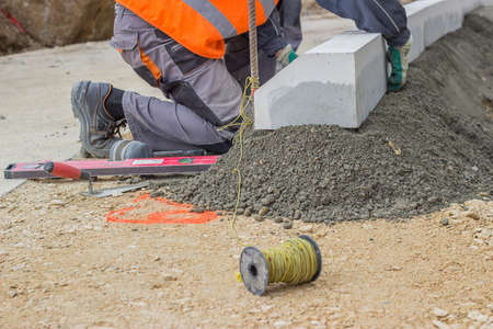 curb: worker installing concrete curb stone and using string with metal stakes to level at sidewalk construction site. Selective focus. Stock Photo