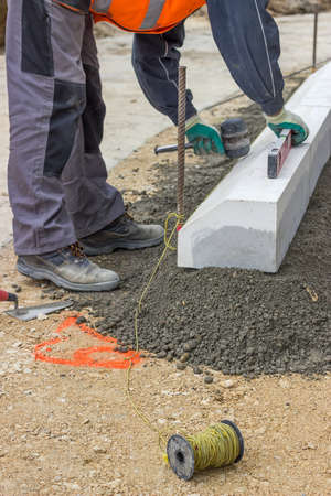 and the stakes: worker installing concrete curb stone and using string with metal stakes to level at sidewalk construction site. Selective focus. Stock Photo