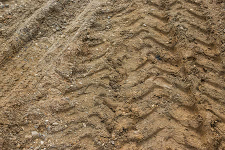 dirtroad: Tractor tyre track closeup on the muddy ground. Selective focus. Stock Photo