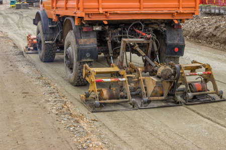 compacting: Plate compactor mounted on truck compacting gravel at road construction site. Selective focus.