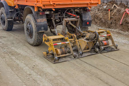 compaction: Plate compactor mounted on truck compacting gravel at road construction site. Selective focus.