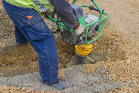 compacting: worker with trench rammer, compacting the sand bedding spread alon the bottom of the cable trench