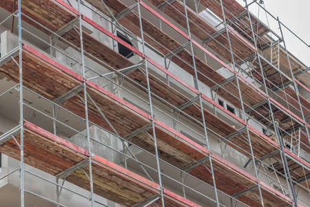 extensive: Extensive scaffolding on a building. Building under the scaffolding. Abstract: construction  industry.