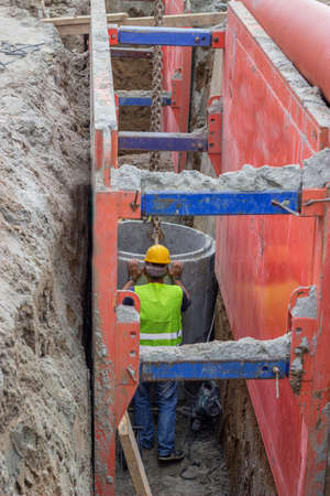 Worker setting concrete pipe in trench. Works on the street reconstruction.