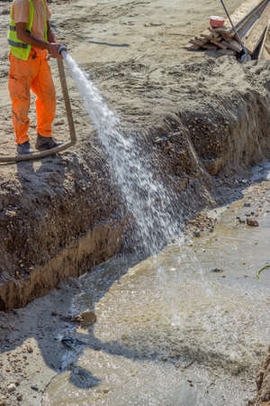compaction: Worker wets the crushed aggregate base course surface before compaction during pipeline construction