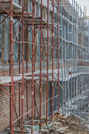 scaffold: Scaffolding on building. Building covered in scaffolding at construction site. Astract: construction industry. Stock Photo