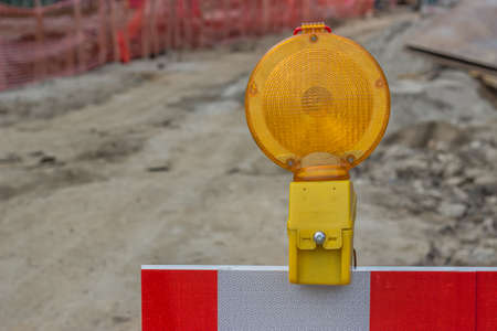 reconstruction: yellow warning ligh on construction barrier sign, street reconstruction sign