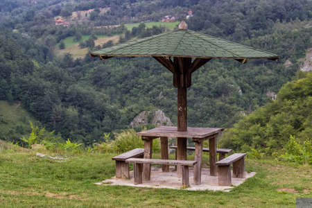 Wooden seating bench with table in nature under wooden umbrella, makes a good resting place. Stock Photo