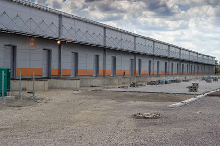 warehouse building: New modern and large warehouse building with warehouse gates, under construction. For semi truck trailer loading and unloading. Stock Photo
