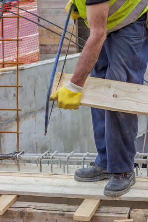 Bulder worker sawing wood board with hand saw, working on formwork installation. Selective focus and motion blur.