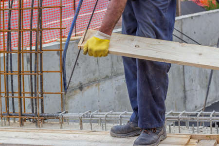 thatcher: Bulder worker sawing wood board with hand saw, working on formwork installation. Selective focus and motion blur.