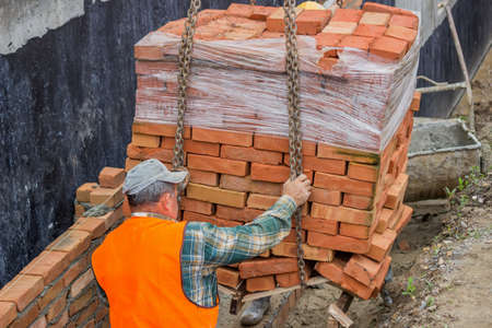delivered: Construction crane delivered clay brick on pallet for builder workers Stock Photo