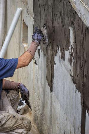 Exterior basement wall waterproofing, worker installing  waterproofing tar sealer. Selective focus and motion blur.