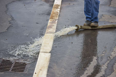 house flood: Man pumping away flood water. Flood water being pumped out of house.