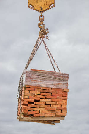 bricklaying: Orange solid clay brick on pallet lifting by construction crane
