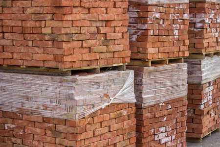 hollow walls: Stacked orange solid clay brick for building construction. Selective focus. Stock Photo