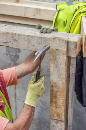 thatcher: Builder hands hammering a nail into a plank, formwork installation at construction site. Selective focus and motion blur.