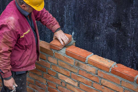 Builder worker laying solid clay brick, bricklaying