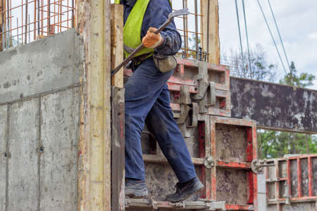 crowbar: builder worker removing formwork elements with crowbar at construction site. Selective focus and motion blur. Stock Photo