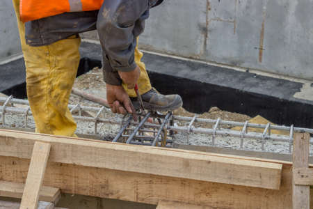 reinforcing bar: Builder worker tying a spacer to a rebar at construction site. Selective focus. Stock Photo
