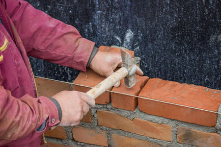 clay brick: Builder worker with bricklayer hammer laying solid clay brick, bricklaying Stock Photo
