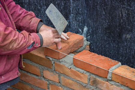 clay brick: Builder worker with trowel laying solid clay brick, bricklaying