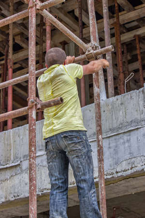 Construction worker set scaffold at the building site. Motion blur.