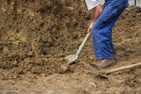 shoveling: Construction worker shoveling dirt,  shoveling ground. Worker with shovel. Selective focus.
