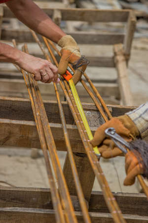 steel making: Measuring and marking steel rods for making beam cages at construction site. Selective focus.